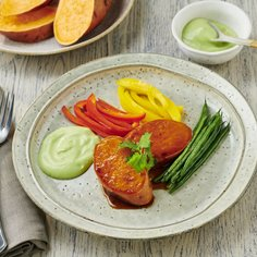 Sweet potato steaks on colourful vegetable strips with avocado cream